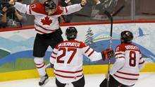 Canada's Sidney Crosby celebrates his game winning goal with Scott Niedermayer and Drew Doughty during overtime period men's ice hockey gold medal final at the 2010 Winter Olympic Games in Vancouver, Sunday, Feb. 28, 2010. (Paul Chiasson)