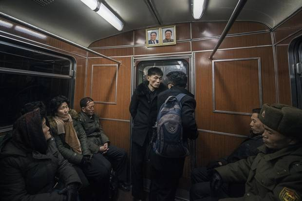 Locals, including a soldier, catch some sleep on their evening train ride home. North Korean law requires that matching portraits of former leaders Kim Il-sung and Kim Jong-il hang at the end of every metro car, as well as in every home, school and workplace in the country. The ever-present personality cult has a sedating effect on city streets, with noise rarely rising above a low thrum.