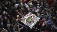Demonstrators grab pieces of a cake as it is passed above their heads during a rally in Tahrir Square in Cairo, Egypt, Friday Feb. 18, 2011. Some thousands of flag-waving Egyptians packed into Tahrir Square for a day of prayer and celebration Friday to mark the fall of longtime leader Hosni Mubarak a week ago and to maintain pressure on the new military rulers to steer the country toward democratic reforms. (Amr Nabil/AP)