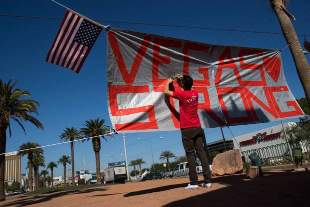 A man writes a note on a 'Vegas Strong' banner at the south end of the Las Vegas Strip.