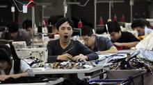 An employee yawns as he works at a garment factory in Humen township, Guangdong province. (SHENG LI/REUTERS)