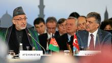 Afghan President Hamid Karzai and his Turkish counterpart, Abdullah Gul, speak in Istanbul on Wednesday at a conference to discuss =approaches to improved security and economic development. (Associated Press)