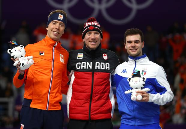 Left to right: Silver medalist Jorrit Bergsma of the Netherlands, gold medalist Ted-Jan Bloemen of Canada and bronze medalist Nicola Tumolero of Italy celebrate during the victory ceremony after the speed skating men's 10,000m.