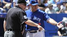 Toronto Blue Jays manager John Farrell argues a call with home plate umpire Bill Welke (L) after Texas Rangers base runner David Murphy was called safe at home plate during the third inning of their MLB American League baseball game in Toronto August 19, 2012. Texas won 11-2. (MIKE CASSESE/REUTERS)
