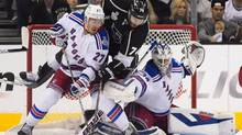 Los Angeles Kings left wing Dwight King, middle, scores between New York Rangers defenseman Ryan McDonagh, left, and goalie Henrik Lundqvist during the third period of Game 2 in the NHL Stanley Cup Final in Los Angeles, Saturday, June 7, 2014. (Mark J. Terrill/AP)