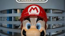 A Super Mario figure greets visitors as children play at Nintendo showroom in Tokyo, Wednesday, July 31, 2013. (Shizuo Kambayashi/AP)