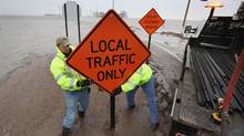Workers erect a sign to let motorists know that County Road 22 near the Red River is closed due to flooding in Harwood, N.D. (Scott Olson/Scott Olson/Getty Images)