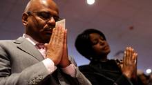 Parishioners hold their offering envelopes and say a pray of thanks for their life's blessings during a Sunday morning worship service at Ebenezer AME Church in Fort Washington, Maryland, March 28, 2010. The congregation, one of America's largest, has been scrambling to raise funds to save the arena-sized sanctuary from potential foreclosure. (JONATHAN ERNST/REUTERS/Jonathan Ernst)
