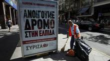 A municipal worker cleans the street next to an election poster for Greece's radical left Syriza party. Pharmaceutical industry sources say drug makers have already discussed with European authorities how to keep Greece supplied with medicines should the country vote to leave the euro zone. (PASCAL ROSSIGNOL/REUTERS)