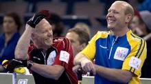 Ontario skip Glenn Howard, left, shares a laugh with Alberta skip Kevin Martin during the evening draw at the Tim Hortons Brier in Edmonton, Alta. Friday, March 8, 2013. (Jonathan Hayward/The Canadian Press)