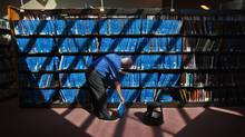 John Elmslie, a librarian at the The Toronto Reference Library shelves books after the library opened its' doors to the public for the first time in two weeks, on Friday March 30, 2012. (JENNIFER ROBERTS/JENNIFER ROBERTS/The Globe and Mail)