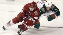 Phoenix Coyotes left winger Lauri Korpikoski, left, of Finland, reaches to gain control of the puck as he is checked by Minnesota Wild defenseman Greg Zanon, right, in the third period of an NHL hockey game Saturday, Dec. 10, 2011 in Glendale, Ariz. The Wild won 4-1. (AP Photo/Paul Connors) (Paul Connors/AP)