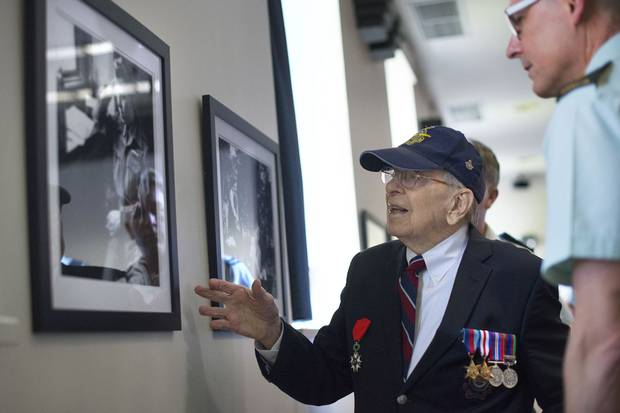 Second World War veteran Jack Ford looks at photographs on display at the Canadian Forces College with the college's commandant, Brigadier-General K.R. Cotten. Mr. Ford, 92, was with the 414 Photo Unit Squadron. He took many of the photographs on display and he developed and printed many more from cameras that were set up in Spitfire fighter planes.