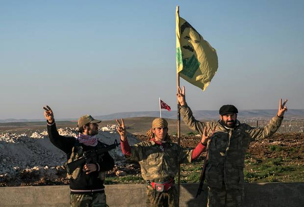Syrian Kurdish militia members of the YPG make a V-sign in Syria's Aleppo province on Feb. 22, 2015.