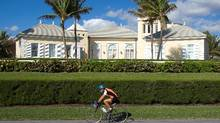 A cyclist rides along South Oceans Boulevard outside Conrad Black's former home in Florida. (Adrian Wyld/THE CANADIAN PRESS/Adrian Wyld)