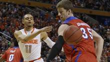 Syracuse's Tyler Ennis (11) passes the ball behind Dayton's Matt Kavanaugh (35) during the first half of a third-round game in the NCAA men's college basketball tournament in Buffalo, N.Y., Saturday, March 22, 2014. (Associated Press)