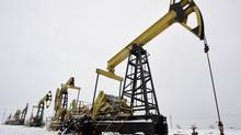 A worker walks past pump jacks at UdmurtNeft's Gremikhinskoye oil field east of Izhevsk near the Ural Mountains December 7, 2007. Russia's largest oil venture with China, UdmurtNeft, will keep output flat to 2012 due to depletion of mature fields but will focus on improving the quality of oil, project leader Rosneft said on Thursday. REUTERS/Sergei Karpukhin (RUSSIA) (SERGEI KARPUKHIN/Sergei Karpukhin/Reuters)