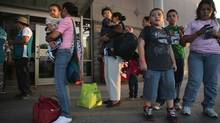 Central American migrants just released from U.S. Border Patrol detention wait at a bus station in McAllen, Tex., on July 25, for their continued journey to various U.S. destinations. (John Moore/Getty Images)