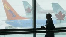 A passenger passes a window at Toronto's Pearson airport on Feb. 5, 2014. (Kevin Van Paassen/The Globe and Mail)