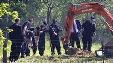 Police officers dig into the ground while searching on the property of Dellen Millard's North Dumfries farm near Cambridge May 30, 2013 to execute a search warrant in connection with the disappearance of Laura Babcock and the suicide of the accused killer's father, Wayne Millard. (Peter Power/The Globe and Mail)