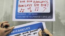 Protestors from the Move Your Money group stick up posters on a branch of Barclays Bank in Westminster central London, July 4, 2012. (OLIVIA HARRIS/Reuters)