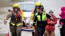 Local residents are rescued by emergency services using a boat in High River, Alta., on June 20, 2013. (CHRIS BOLIN FOR THE GLOBE AND MAIL)