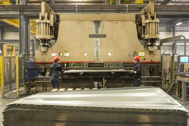 Workers at Samuel, Son & Co are running a hydraulic brake press, to form box car doors.