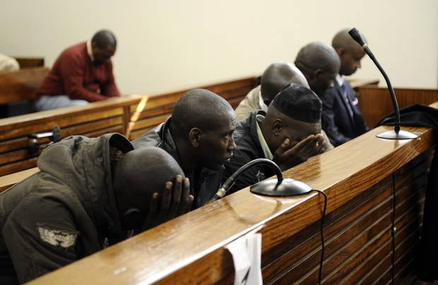 Six men charged with attempting to kill Rwanda's former army chief Faustin Kayumba Nyamwasa (unseen) sit at court in Johannesburg on July 10, 2012.