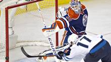 Winnipeg Jets' James Wright (17) hits the post as Edmonton Oilers goalie Devan Dubnyk (40) looks on during second period NHL hockey action in Edmonton, Alta., on Tuesday October 1, 2013. (JASON FRANSON/THE CANADIAN PRESS)