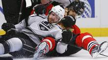 Chicago Blackhawks' Michal Handsuz loses his helmet while falling with Los Angeles Kings' centre Mike Richards in the first period during Game 1 of their NHL Western Conference final hockey playoff game in Chicago, Illinois, June 1, 2013. (Reuters)