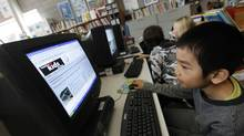 Hao Chen Yu, 8 reads the news as one of the Teaching The Kids News developer, teacher Kathleen Tilly works with other students in the library at Eglinton Public School in Toronto. (Deborah Baic/The Globe and Mail/Deborah Baic/The Globe and Mail)