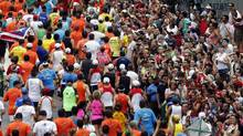 WITH FLYING COLOURS: Spectators take photographs of runners in the annual Sao Silvestre Run winding through the streets of Sao Paulo, Brazil. (PAULO WHITAKER/REUTERS)