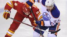 Edmonton Oilers' Taylor Hall, right, battles with Calgary Flames' Mark Giordano during third period NHL action in Calgary, Alta., Wednesday, April 3, 2013. (Larry MacDougal/THE CANADIAN PRESS)
