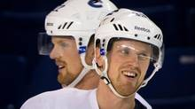 Vancouver Canucks' Henrik Sedin, right, and his twin brother Daniel Sedin, both of Sweden, skate during an informal hockey practice at the University of British Columbia in Vancouver, B.C., on Tuesday January 8, 2013. (DARRYL DYCK/THE CANADIAN PRESS)