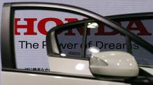 Logo of Honda Motor Co is seen through car doors at the company showroom in Tokyo April 27, 2012. (KIM KYUNG-HOON/REUTERS)