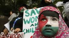 A Filipino Muslim girl, with the colours of the Palestinian flag painted on her face, stands near her mother during a rally held by the Anak Mindanao (Children of Mindanao) Party List group outside the Israeli embassy in Manila on July 15, 2014. (ERIK DE CASTRO/REUTERS)