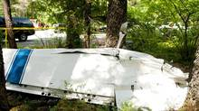 The severed wing of a Cessna 150 lies near the parking lot of Narin Falls Provincial Park, near Pemberton, about 50 kilometres north of Whistler, after a collision between it and a glider on Saturday, June 29, 2013. (David Buzzard/THE CANADIAN PRESS)