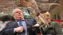 J.P. Moczulski (Toronto mayor Rob Ford holds a great horned owl named Alexandra at the Toronto Sportmen's show at the Direct Energy centre in Toronto, February 7, 2013. for The Globe and Mail))