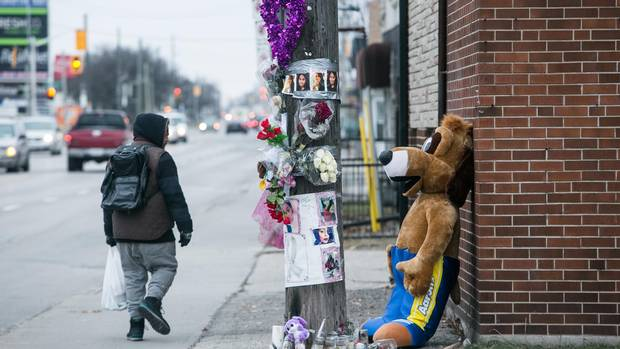 A passerby glances at a memorial for Holly Hamilton at an intersection not far from where her body was found in the trunk of her car in Hamilton.