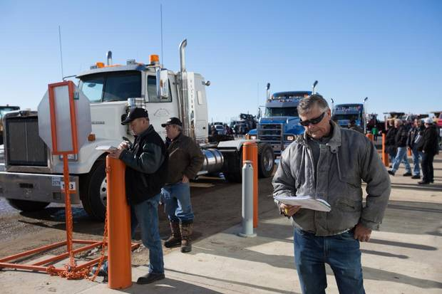Dave Kuchera keeps an eye on selling prices as semi trucks go up for bidding during an auction at Ritchie Bros. in Nisku.