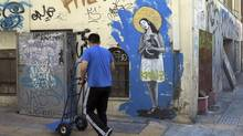 A man pushes a trolley cart as he walks past a wall covered with graffiti in central Athens July 1, 2012. (PASCAL ROSSIGNOL/REUTERS)