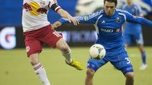 New York Red Bulls' Dax McCarty, left, and Montreal Impact's Andrea Pisanu battle for possession of the ball during first half of Major League Soccer action at the Olympic Stadium in Montreal on Saturday March 23, 2013. (Peter McCabe/THE CANADIAN PRESS)