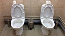 In this photo taken Saturday, Feb. 1, 2014, two female toilets sit side-by-side at the security screening facility outside the Main Press Center at the 2014 Winter Olympics, in Sochi, Russia. Side-by-side toilets in a single bathroom caused a social media sensation last month when they were discovered at the biathlon course of the Sochi Olympics, swiftly becoming a national joke in Russia. The Sochi organizing committee initially denied knowledge of the second twin toilet, and it has not been able to say whether the loo-loo was built by design or resulted from an error during the plumbing process. (Associated Press)