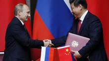 Russia's President Vladimir Putin, left, and China's President Xi Jinping shake hands after signing an agreement during a bilateral meeting at the Xijiao State Guesthouse ahead of the fourth Conference on Interaction and Confidence Building Measures in Asia (CICA) summit, in Shanghai, China Tuesday, May 20, 2014. (Carlos Barria/AP)