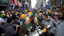 Jason and Nicole Dickson, from Calgary, carry the Grey Cup through the streets of Toronto on Sunday during the Sun Life Grey Cup Fan March. (Matthew Sherwood for The Globe and Mail)