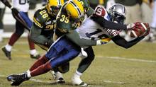 Montreal Alouettes' S.J. Green stretches for a first down while Edmonton Eskimos' Agustin Barrenechea and Siddeeq Shabazz try to pull him down during the first half of their CFL football game in Edmonton October 31, 2008.  (Reuters)