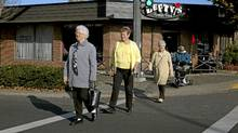 Seniors Sophia Thornley-NIx (left,) Wendy Haines (with the cane and yellow top) , Joan Grange (beige coat and brown pants, and Dorothy Bennett (on the scooter ) cross the street near the Qualicum Beach Seniors Centre on Oct. 24, 2011. (Gordon Ross/Gordon Ross for the Globe and Mail)
