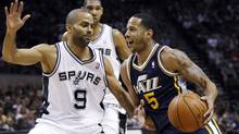 Utah Jazz guard Devin Harris, right, drives on San Antonio Spurs guard Tony Parker as centre Tim Duncan watches during the first half of their Western Conference quarter-final playoff basketball game in San Antonio on Sunday. (MIKE STONE)