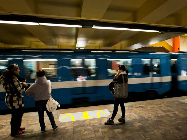 Passengers stand while a Montreal Metro train passes through a station in Montreal, Quebec, Canada, on Saturday, Nov. 5, 2011. The Montreal Metro system is currently Canada's busiest subway system in total daily passenger usage, serving an average of 1,111,700 daily passengers on an average weekday. Photographer: