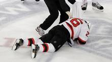 New Jersey Devils' Patrik Elias (26), of the Czech Republic, lays on the ice after an apparent hit to the face as trainer Richard Stinziano checks on him during the first period of Game 1 of their NHL hockey Stanley Cup Eastern Conference final playoff against the New York Rangers, Monday, May 14, 2012, at New York's Madison Square Garden. (Julio Cortez/AP/Julio Cortez/AP)
